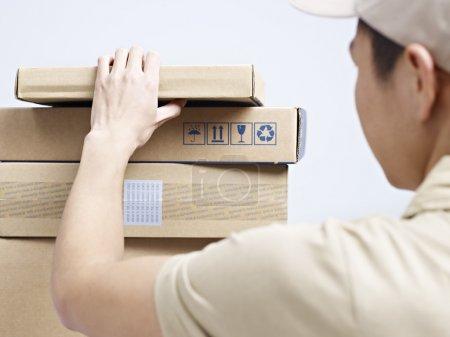 Photo pour Male asiatique courier travailleur de la compagnie vérification des paquets pour être livré. - image libre de droit