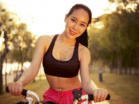 Photo pour Young and beautiful asian woman riding bicycle outddors in park at sunset, smiling and cheerful, fitness, sport and exercise, healthy life and lifestyle concept. - image libre de droit