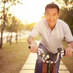 Mid-adult asian man riding bicycle outdoors at sun...