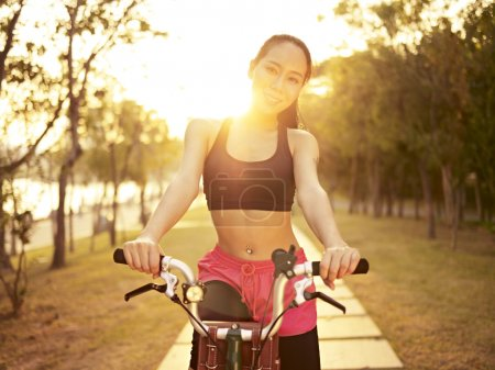 Photo for Young and beautiful asian woman riding bicycle outddors in park at sunset, smiling and cheerful, fitness, sport and exercise, healthy life and lifestyle concept. - Royalty Free Image