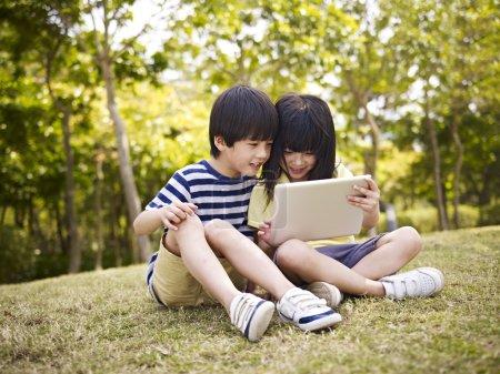Photo pour Petite asiatique fille et garçon assis sur herbe en utilisant numérique tablette à l'extérieur dans un parc . - image libre de droit