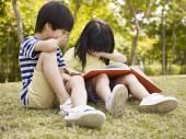Asijské děti čtení knihy venku