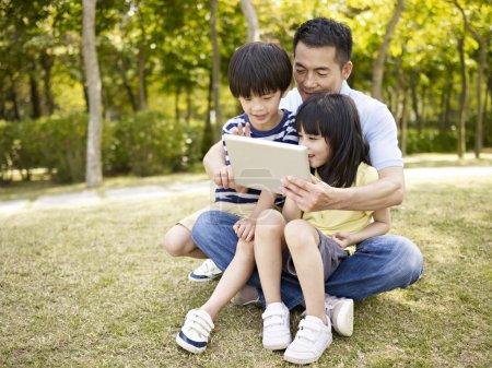 Photo pour Père asiatique et deux enfants assis sur l'herbe regardant tablette ordinateur, en plein air dans un parc . - image libre de droit