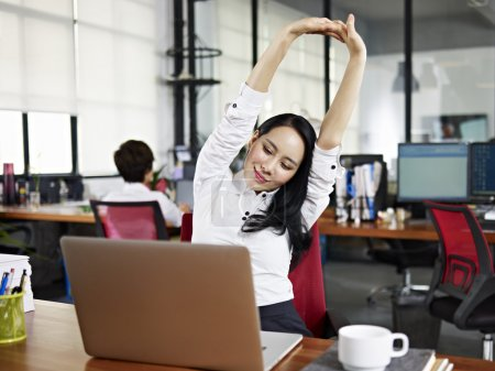 Asian businesswoman looking at work on laptop computer with satisfaction and stretching arms in the air.