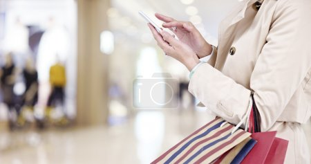 woman using cellphone while shopping