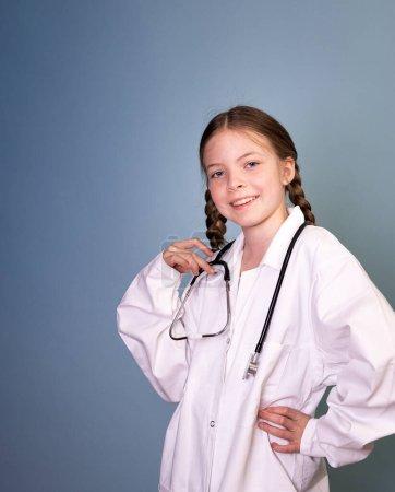 Photo pour Jolie fille avec deux tresses est habillé comme médecin et posant avec stéthoscope sur fond bleu, professions concept - image libre de droit