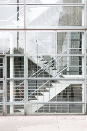 Interior of a modern glass building with stairs.