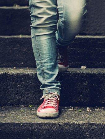 Photo pour Petite fille en baskets rouges et jeans faisant le premier pas dans les escaliers - image libre de droit