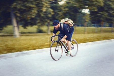 Photo pour Jeunes barbus hipster conduire vite un vélo à pignon fixe sur la route. - image libre de droit