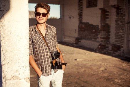 man with vintage camera posing outdoor