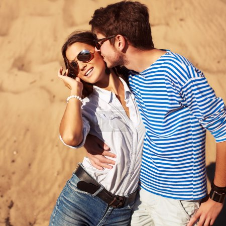 man kissing woman in summer vacation