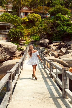 woman in white dress walking on pier
