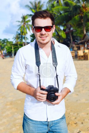 Photo for Outdoor fashion portrait of young handsome man photographer with camera posing on the tropic island beach smiling and having fun in summer - Royalty Free Image