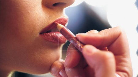 Photo for Cropped view of makeup artist applying lip pencil on lips of model - Royalty Free Image