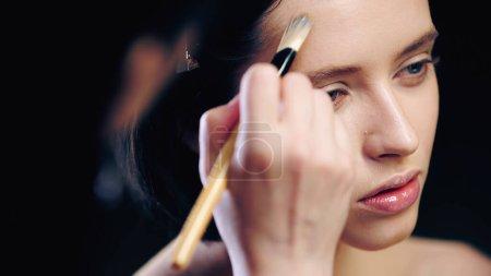 Photo pour Maquilleuse floue faisant visage contouring de jeune femme avec pinceau cosmétique - image libre de droit