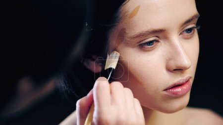 Photo pour Maquilleur flou faisant visage contouring de jeune modèle avec pinceau cosmétique - image libre de droit