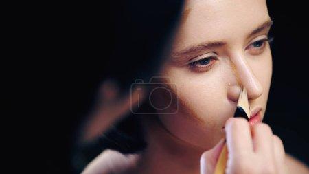 Photo pour Maquilleuse floue faisant visage contouring de la femme avec pinceau cosmétique - image libre de droit
