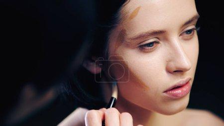 Photo pour Maquilleur flou faisant visage contouring du modèle avec pinceau cosmétique - image libre de droit