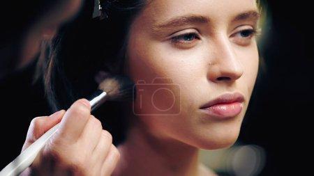 Photo pour Maquilleuse appliquant de la poudre visage sur femme brune - image libre de droit