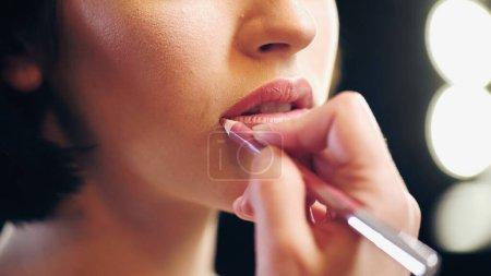 Photo pour Vue recadrée du maquilleur flou appliquant crayon à lèvres sur les lèvres de la femme - image libre de droit