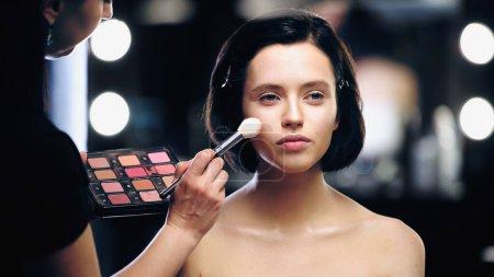 Make-up-Artist hält Palette und trägt Textmarker auf Gesicht der Frau auf