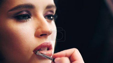 Photo for Makeup artist applying shiny lip gloss on lips of model isolated on black - Royalty Free Image