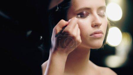 Photo pour Maquilleur flou appliquant ombre à paupières foncée avec pinceau cosmétique sur les paupières du modèle aux yeux fermés - image libre de droit