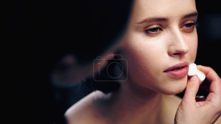 Photo for Blurred makeup artist applying face foundation on model with cosmetic sponge - Royalty Free Image
