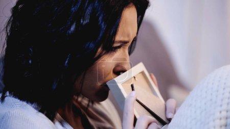 Photo pour Portrait d'une femme bouleversée tenant un cadre photo près de la bouche et pleurant sur un canapé à la maison - image libre de droit