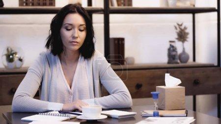 Photo pour Femme réfléchie assis sur la table avec une tasse de café, calculatrice, verre de sable et cahiers avec stylo à la maison - image libre de droit