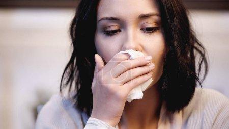 Photo pour Vue rapprochée de femme bouleversée essuyant le nez avec une serviette en papier à la maison - image libre de droit