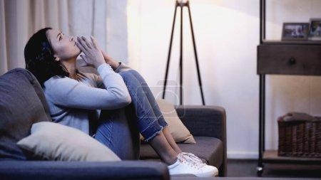 Photo pour Femme déprimée en vêtements décontractés assis sur le canapé avec les mains priantes près de la bouche à la maison - image libre de droit