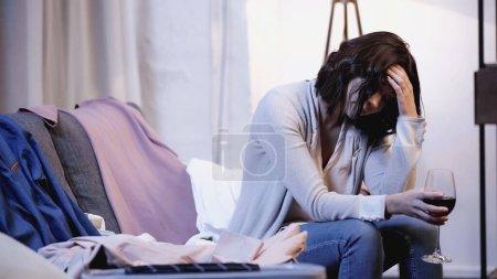 Verärgerte Frau sitzt mit Glas Rotwein in der Nähe von Männerkleidern auf Sofa und hält daheim die Hand am Kopf