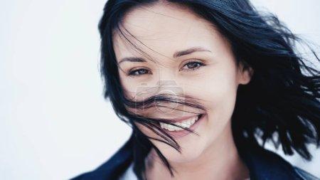 Photo pour Femme souriante avec les cheveux sur le vent couvrant visage sur fond gris - image libre de droit