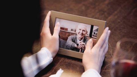 Photo pour Vue partielle des mains féminines tenant le cadre photo avec la photo de l'homme âgé à la maison - image libre de droit