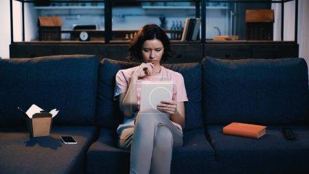 Photo pour Femme brune utilisant une tablette numérique alors qu'elle est assise sur un canapé près d'un smartphone, d'un livre et d'une boîte en carton - image libre de droit