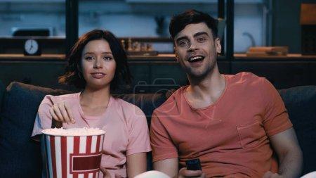 Photo pour Femme heureuse tenant seau de maïs soufflé et regarder le film de comédie avec petit ami joyeux - image libre de droit