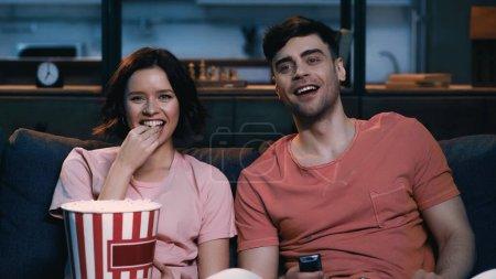 Photo pour Femme heureuse manger du pop-corn et regarder un film de comédie avec petit ami joyeux - image libre de droit