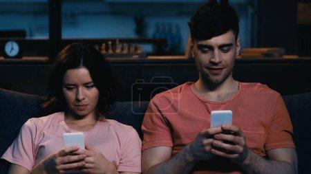 Photo pour Homme et femme textos sur les téléphones cellulaires dans le salon moderne - image libre de droit