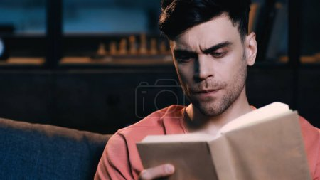 Photo for Focused man reading book at home - Royalty Free Image