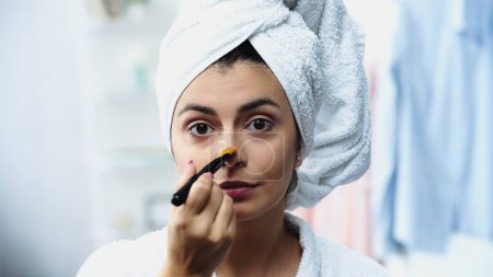 Photo pour Jeune femme avec la tête enveloppée dans une serviette appliquer fond de teint sur le nez avec brosse cosmétique dans la chambre - image libre de droit