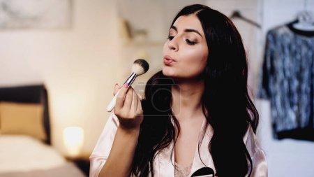Photo pour Jeune femme en soie rose peignoir soufflant sur pinceau cosmétique dans la chambre - image libre de droit
