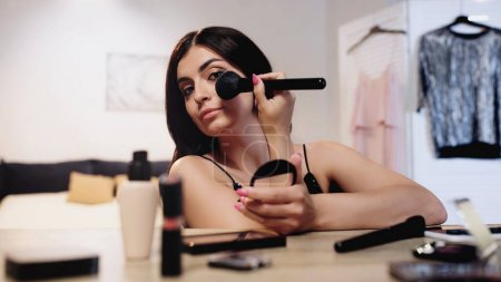 young woman applying face powder with cosmetic brush near table with decorative cosmetics in bedroom