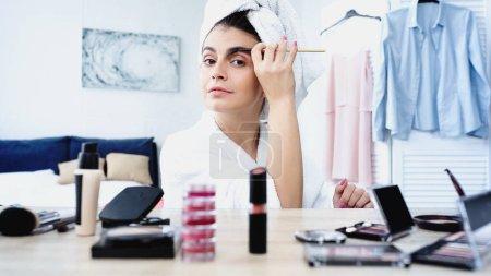 Photo pour Jeune femme en peignoir avec tête enveloppée dans une serviette de style sourcil avec brosse près de la table avec des cosmétiques décoratifs dans la chambre - image libre de droit