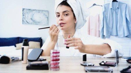 Photo pour Jeune femme en peignoir tenant rouge à lèvres et l'appliquant avec pinceau cosmétique sur les lèvres dans la chambre - image libre de droit