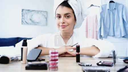 Photo pour Jeune femme souriante assise avec une brosse cosmétique près de la table avec des cosmétiques décoratifs dans la chambre - image libre de droit