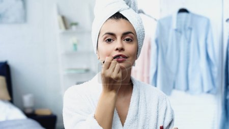 young woman in bathrobe with head wrapped in towel applying lipstick with cosmetic brush in bedroom