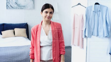 Photo for Confused young woman standing in white blouse and pink blazer near hangers with clothes in bedroom - Royalty Free Image