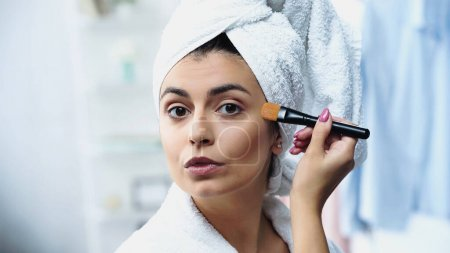 young woman with head wrapped in towel applying foundation on face with cosmetic brush in bedroom
