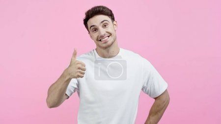 Photo pour Homme souriant en t-shirt blanc regardant la caméra et montrant pouce vers le haut isolé sur rose - image libre de droit